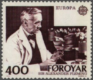 Even in his postage stamp he is surrounded by precariously stacked petri dishes.